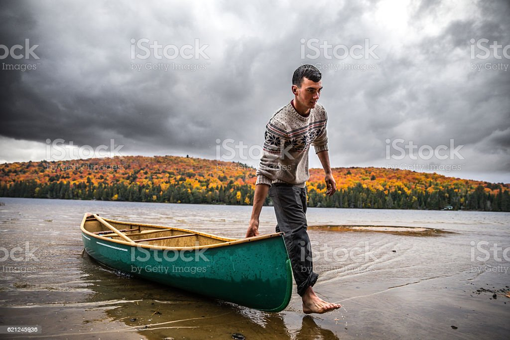 Taking canoe out of water at the end the day stock photo