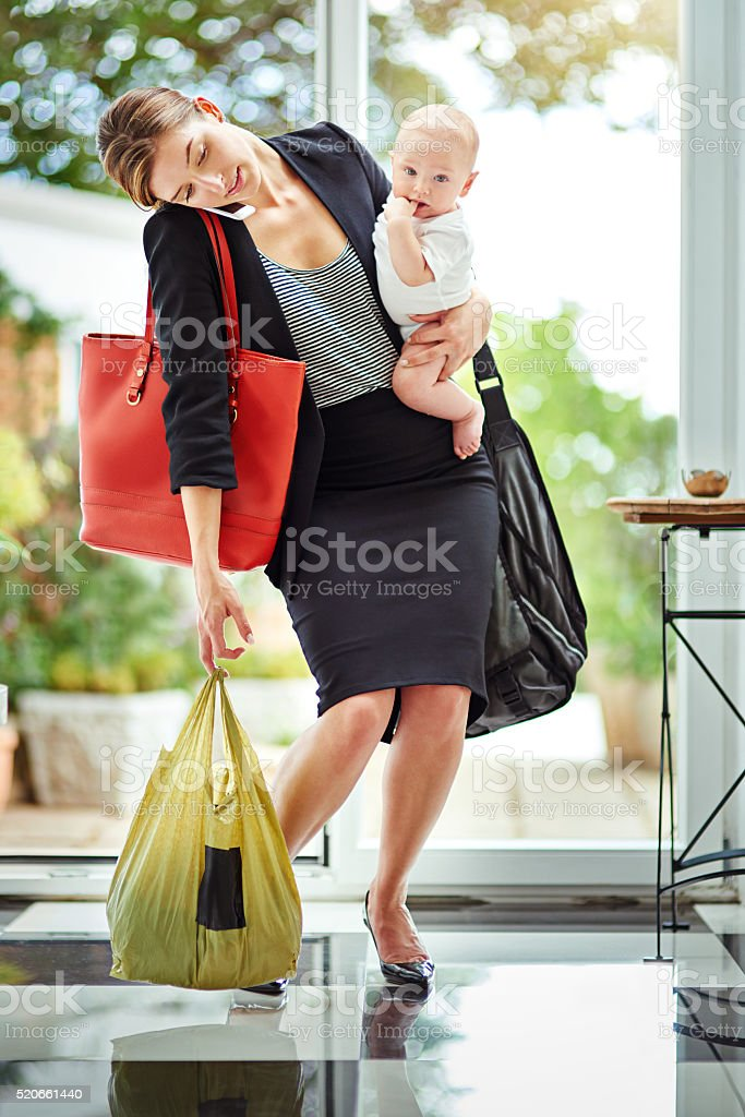 Taking care of her baby and her clients stock photo