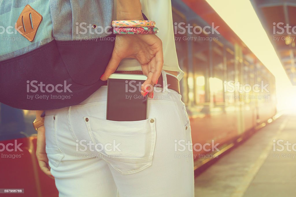Taking cellphone from/to the pocket on railway station. stock photo
