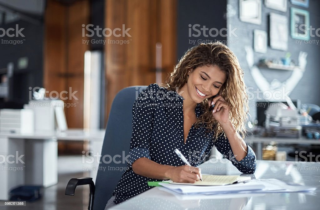 Taking notes of her business call stock photo