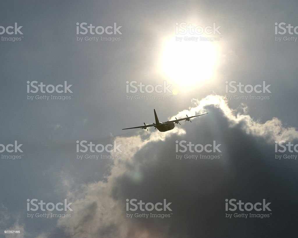 C130G taking off into sun stock photo