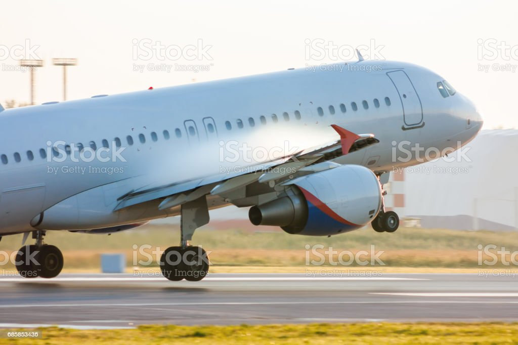 Taking off passenger airplane with condensate vapor on wings stock photo