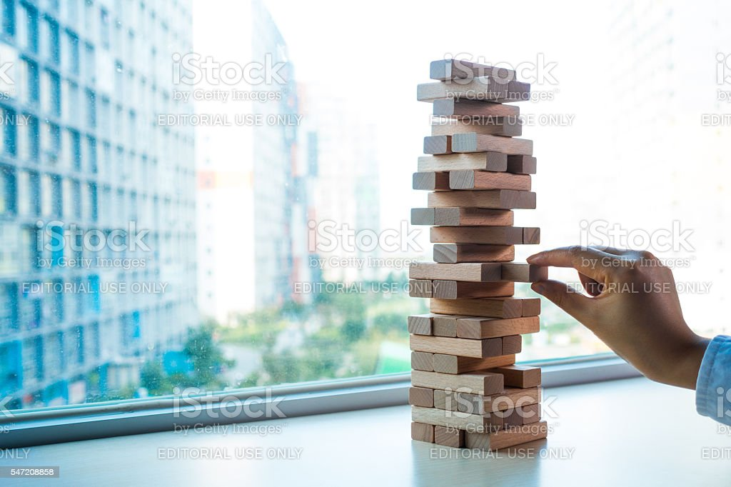 Taking one block from wooden blocks tower stock photo