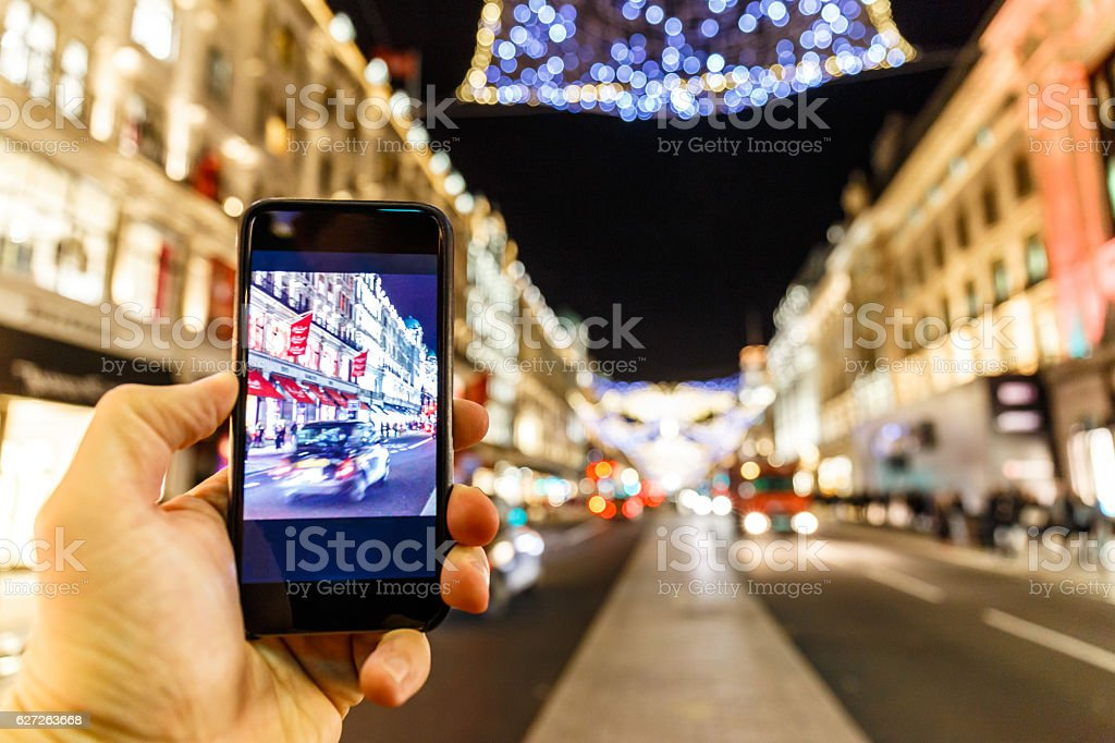 Taking photo of Christmas London on mobile phone stock photo