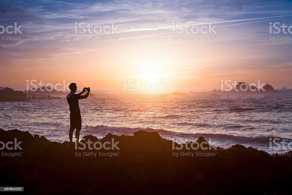 Taking photo of sunset on the sea stock photo