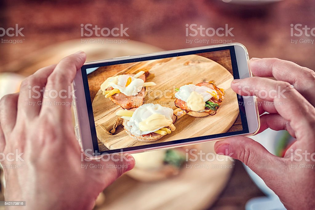 Taking Photo with Smartphoen of Egg Benedict For Breakfast stock photo