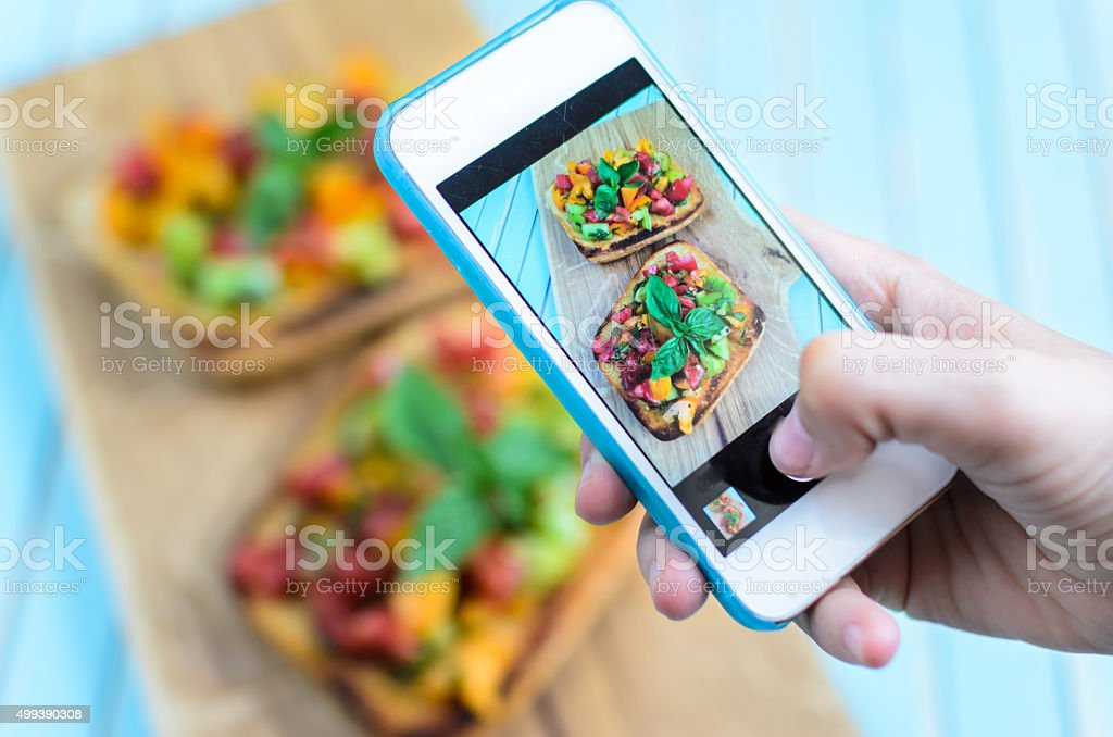 Taking photo with smartphone of bruschetta on wooden cutting board stock photo