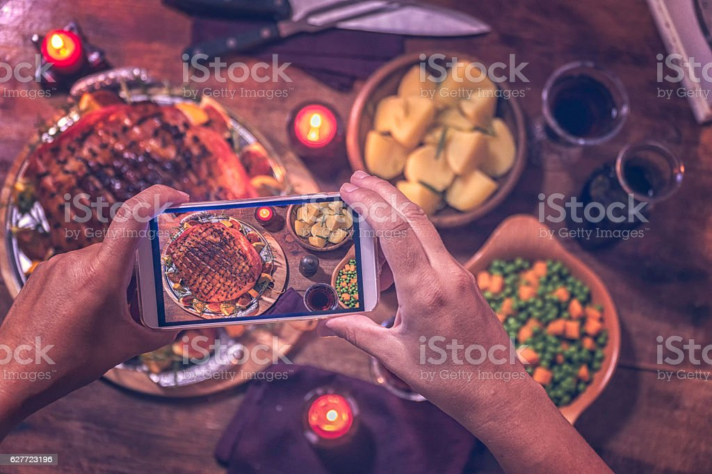 Taking Photo with Smartphone of Glazed Holiday Ham Dinner stock photo