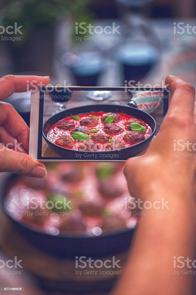 Taking Photo with Smartphone of Meatballs with Tomato Sauce stock photo