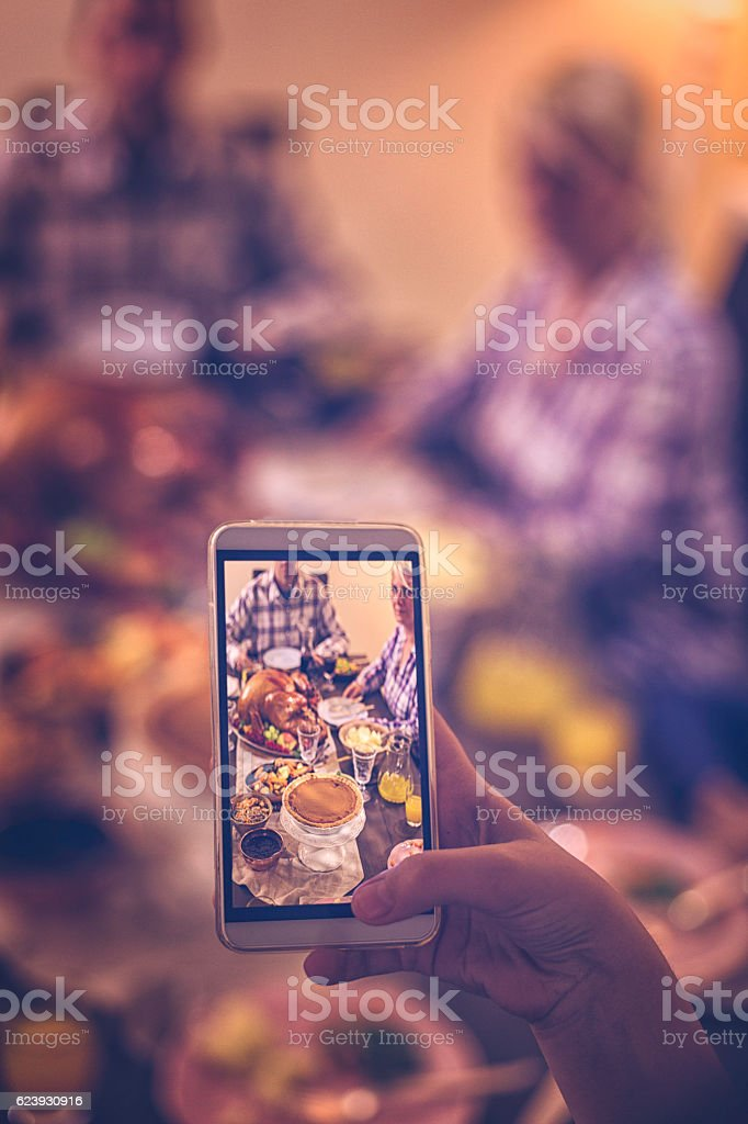 Taking Photo with Smartphone of Traditional Holiday Stuffed Turkey Dinner stock photo