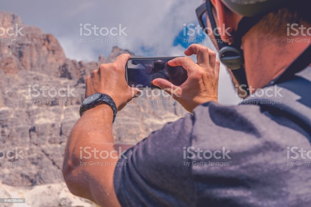 Taking Photos Using Smartphone Device. Caucasian Biker in Bike Helmet Taking Picture of the Scenic Mountain Place. stock photo