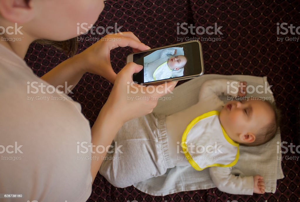 Taking picture of a baby boy using smartphone stock photo