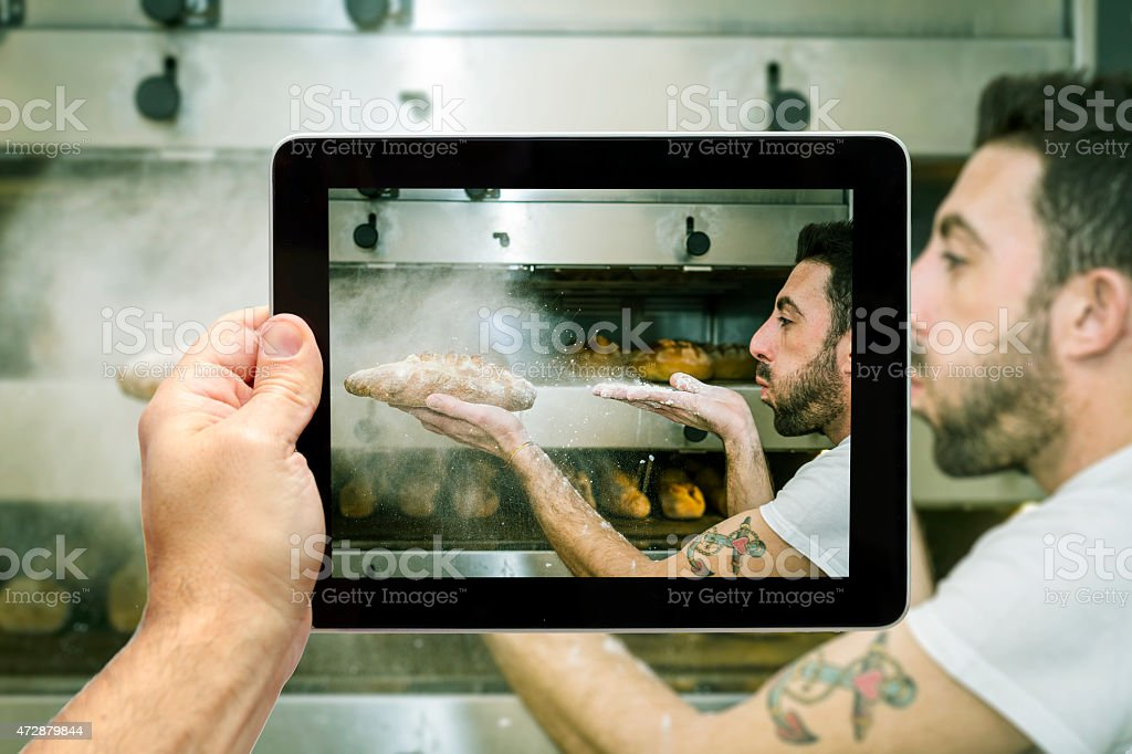 Taking picture of baker that blows flour on bread stock photo