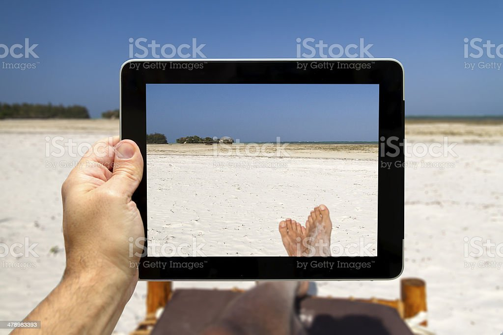 Taking picture with digital tablet from a beach in Zanzibar stock photo