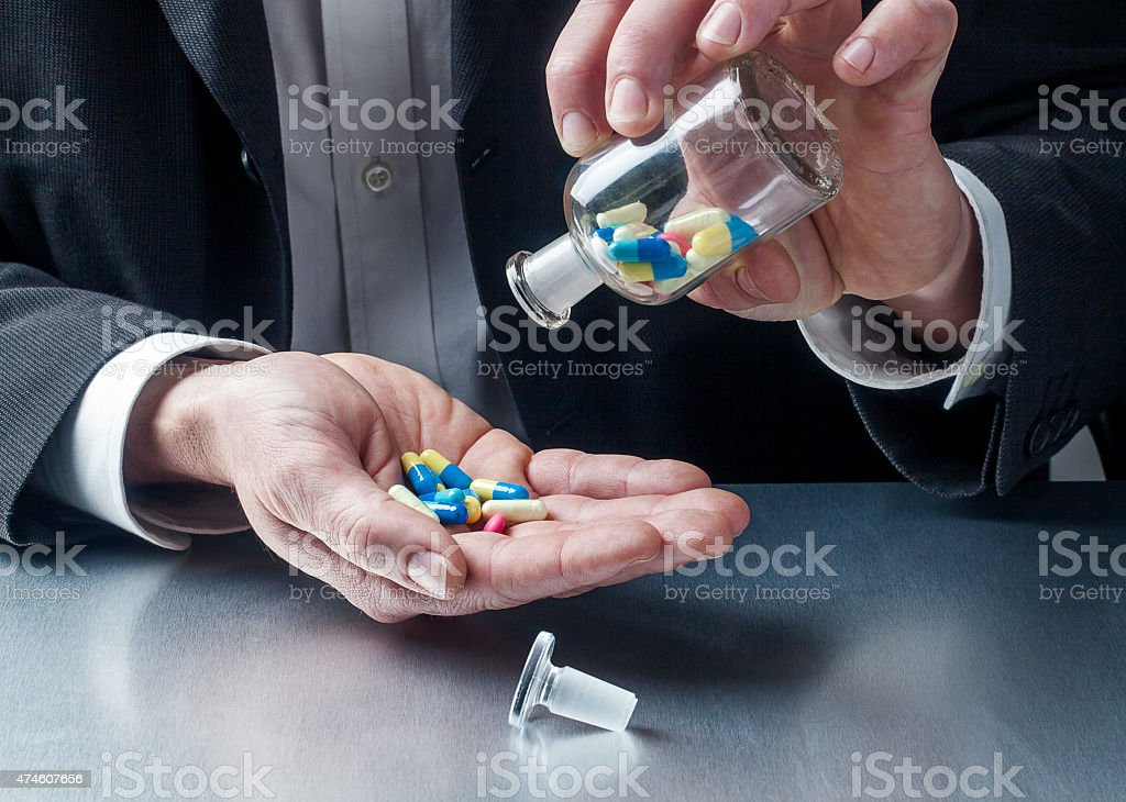 taking pills on the workplace stock photo