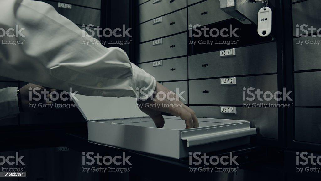 Taking something valuable from deposit box stock photo
