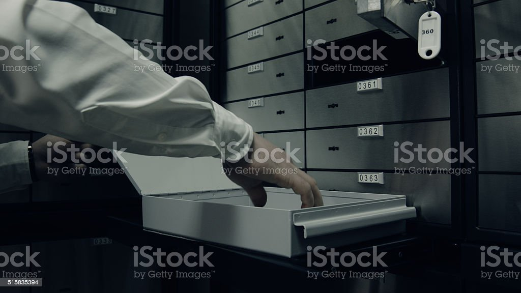 Taking something valuable from deposit box stock photo