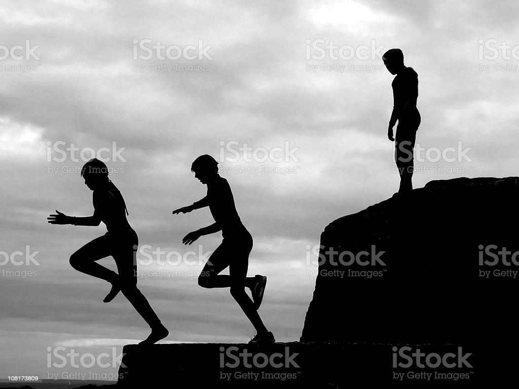 Taking the plunge - boys cliff diving. royalty-free stock photo