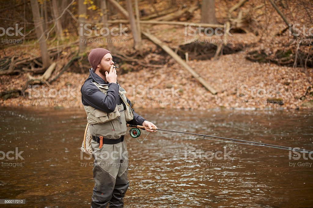 Taking time out in nature with his fishing rod stock photo