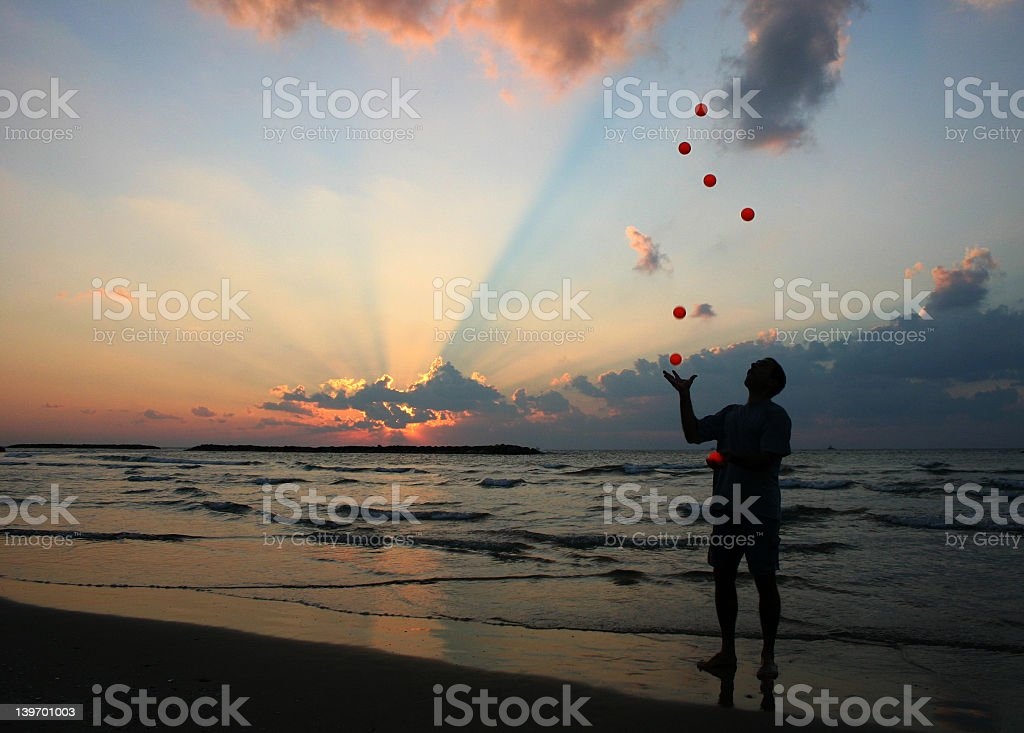 A talented juggler juggling in front of a body of water stock photo