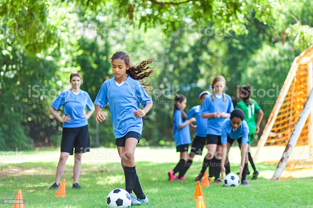 Talented soccer player kicks ball around practice cones stock photo