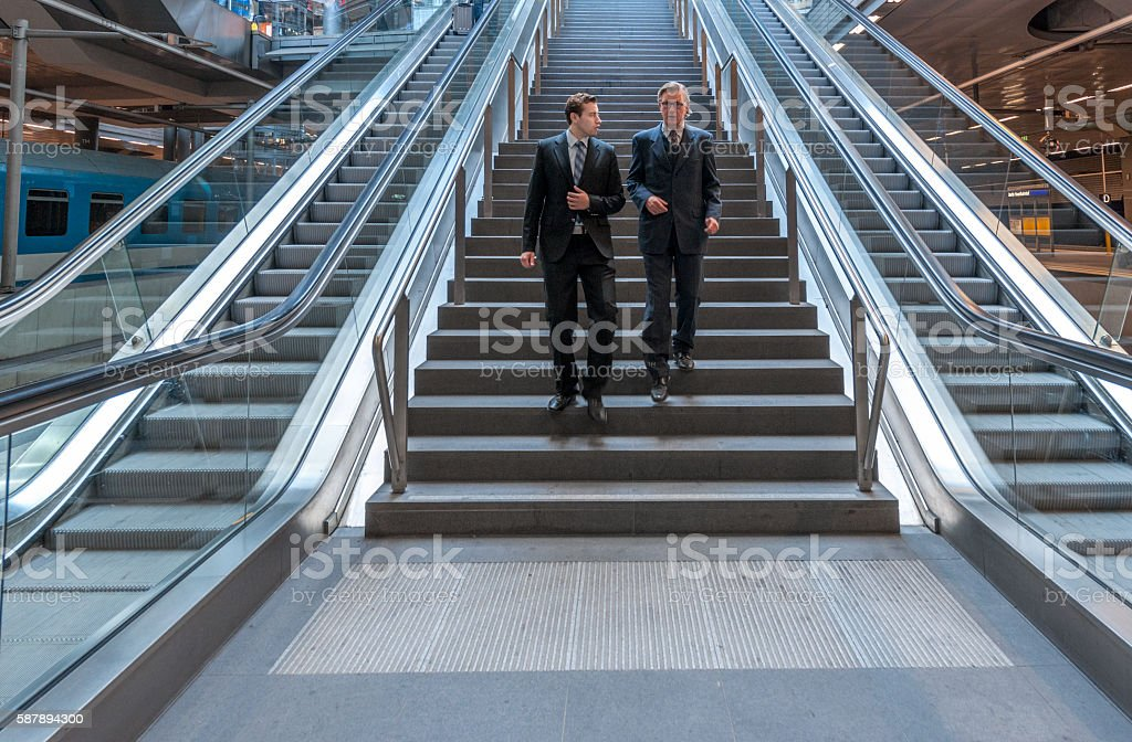 talking businessmen walking down the stairs in modern railroad station stock photo