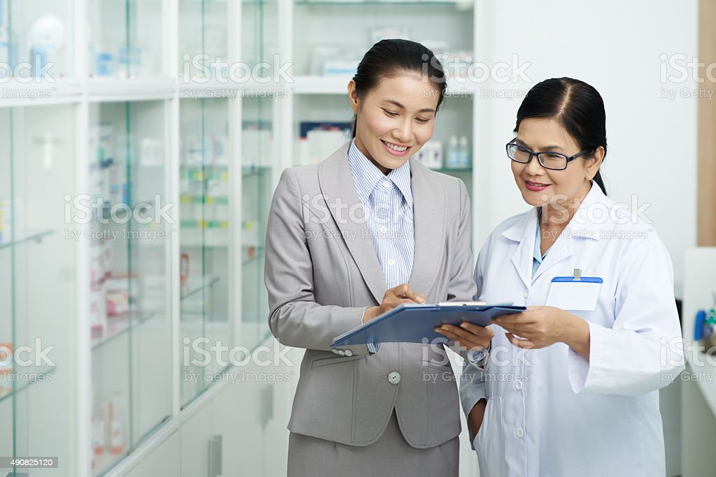 Talking to pharmacy worker stock photo
