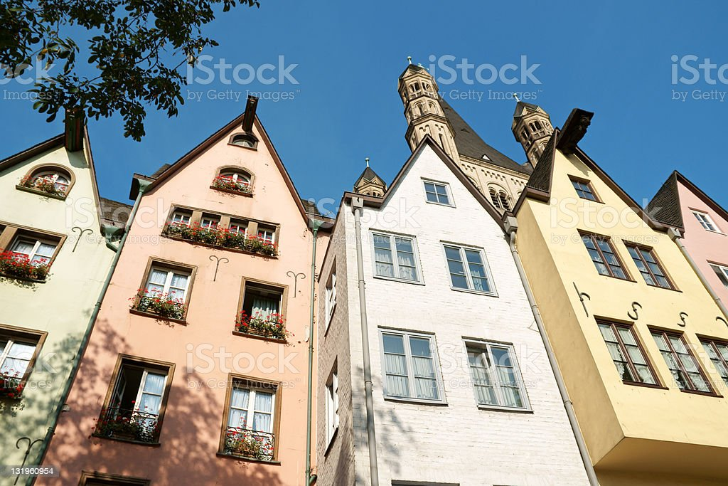 Tall ancient pastel colored houses with blue sky in Cologne stock photo