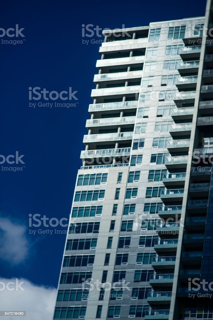Tall apartment standing diagonally against the navy sky. stock photo