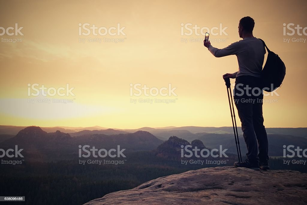 Tall backpacker with phone in hand. Spring daybreak in mountains. stock photo