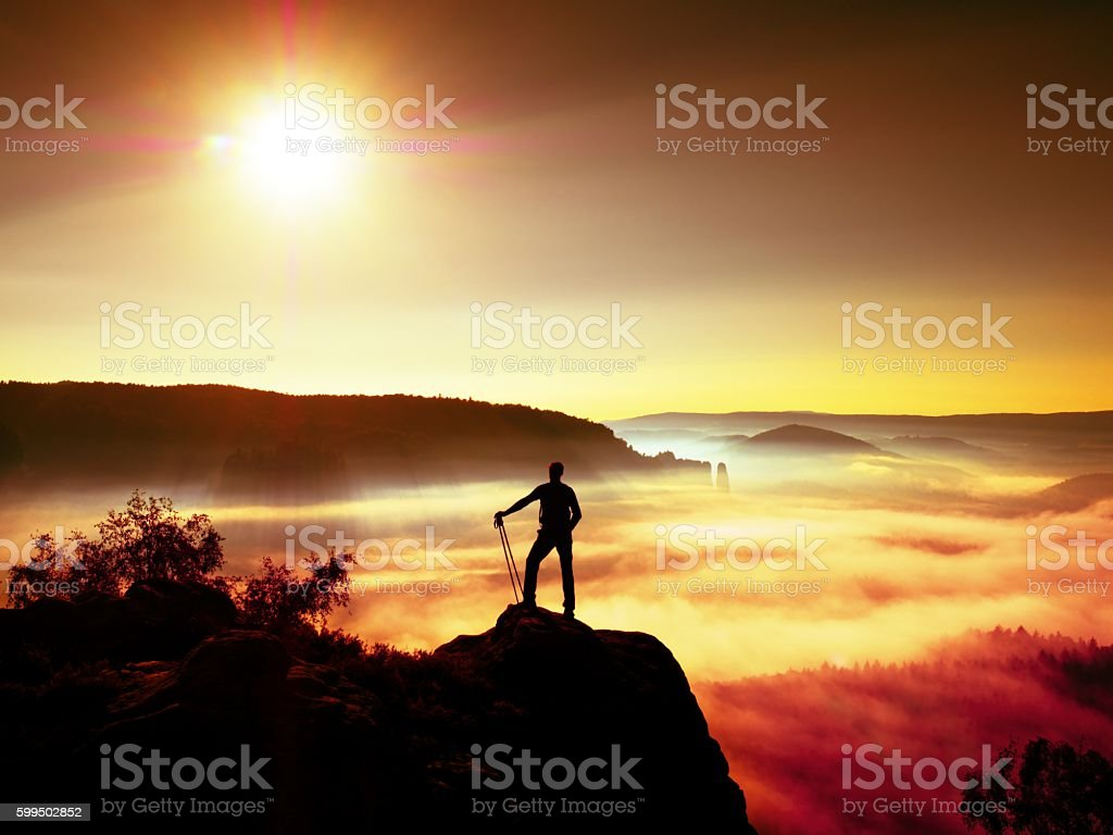 Tall backpacker with poles in hand. Sunny daybreak in rocks stock photo