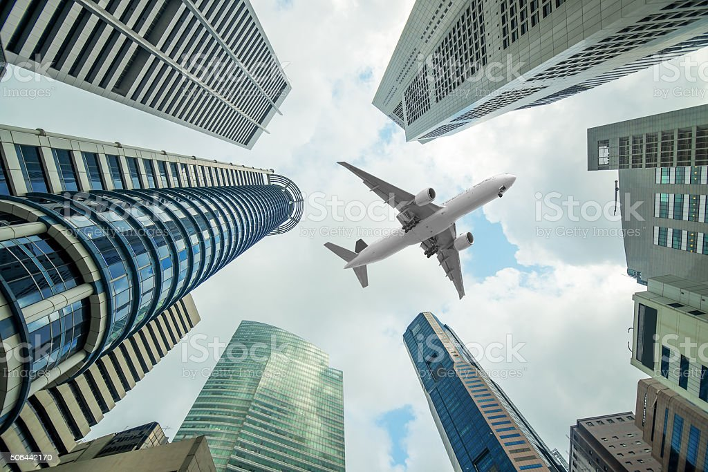 Tall city buildings and a plane flying overhead in morning stock photo