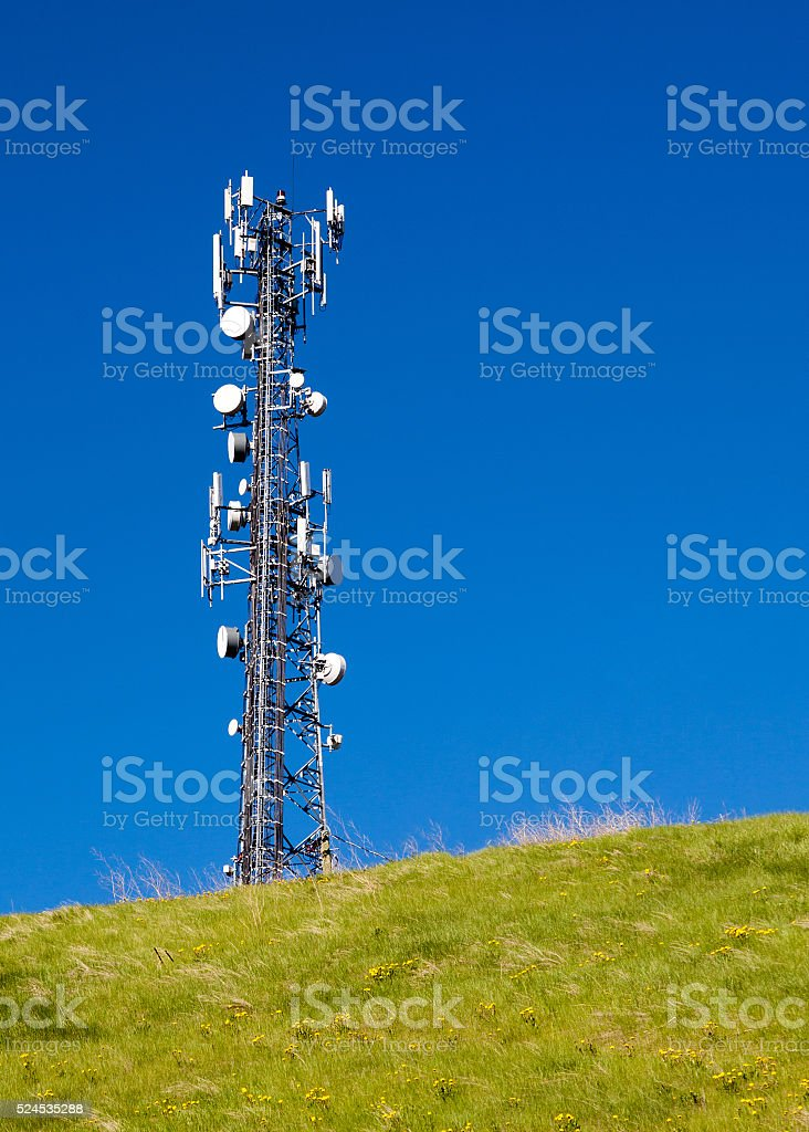 Tall Communication Tower on a Hill With Blue Sky stock photo