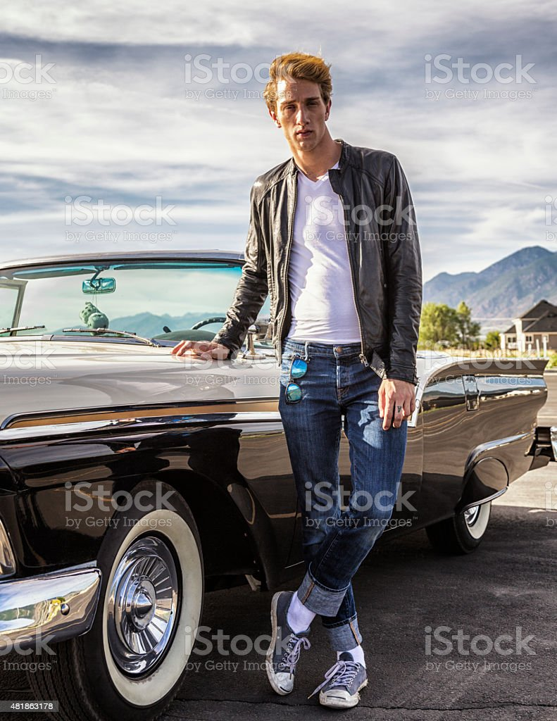 Tall Cool Fifties Greaser Guy Standing With Convertible Classic Car stock photo