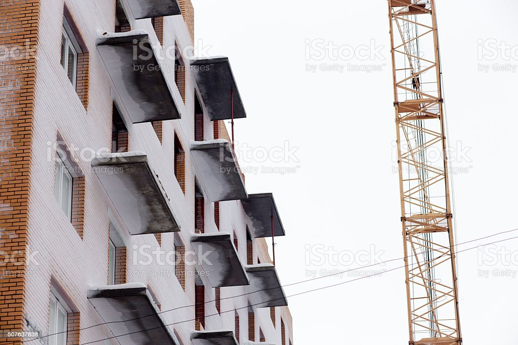 Tall crane and balconies of building under construction on blue stock photo