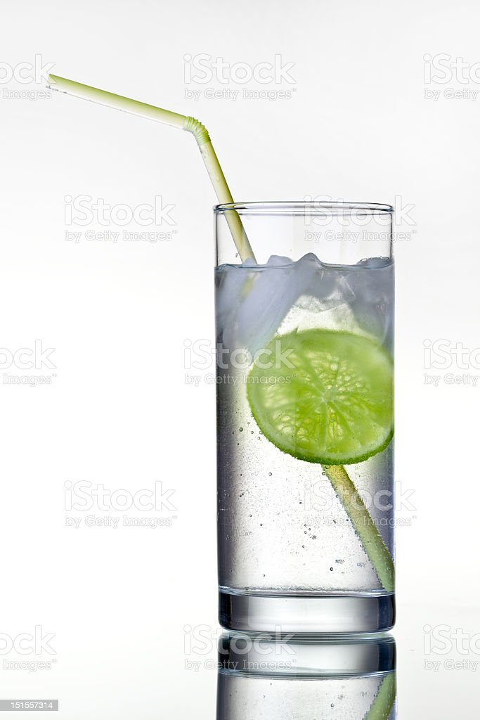 A tall glass of gin and tonic with a lime and a straw royalty-free stock photo