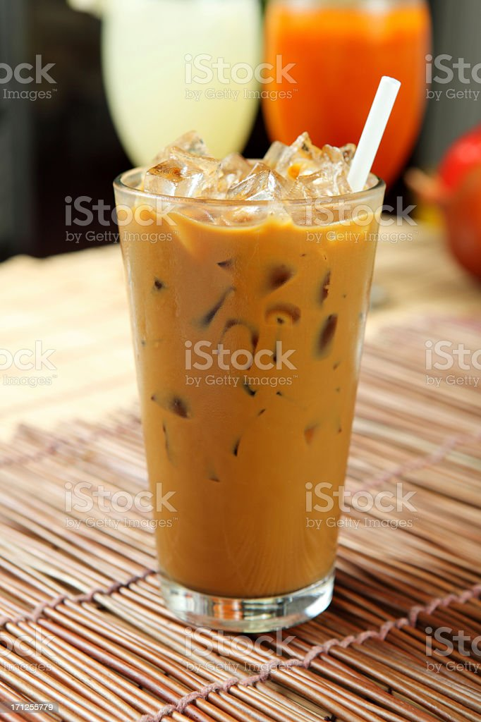 A tall glass of iced coffee served on a table with a straw royalty-free stock photo