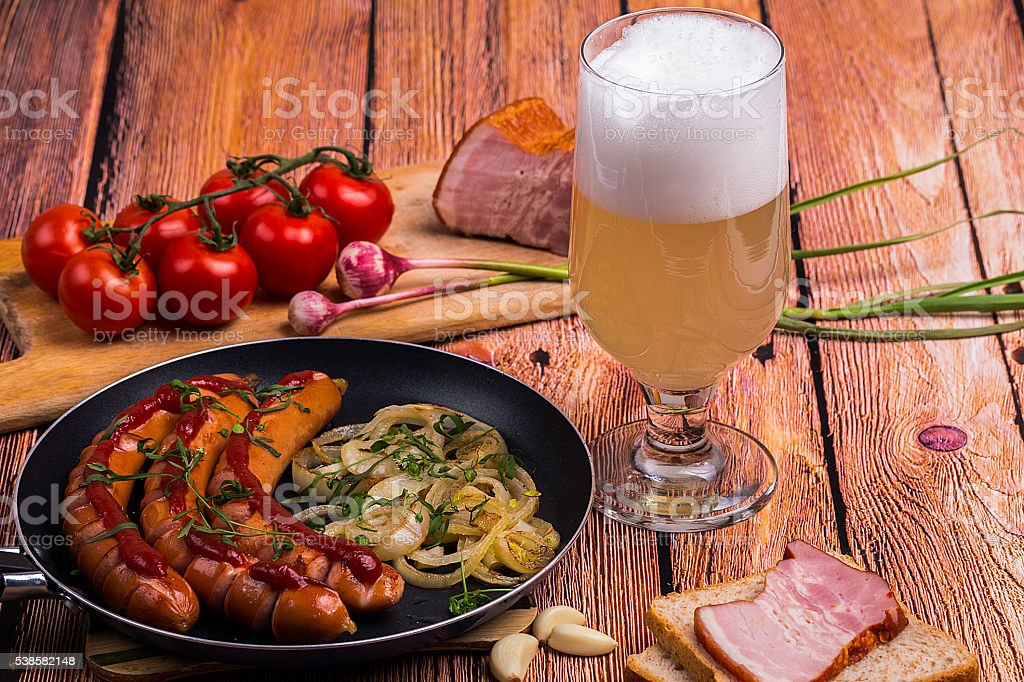 Tall glass with unfiltered beer and fried sausages stock photo