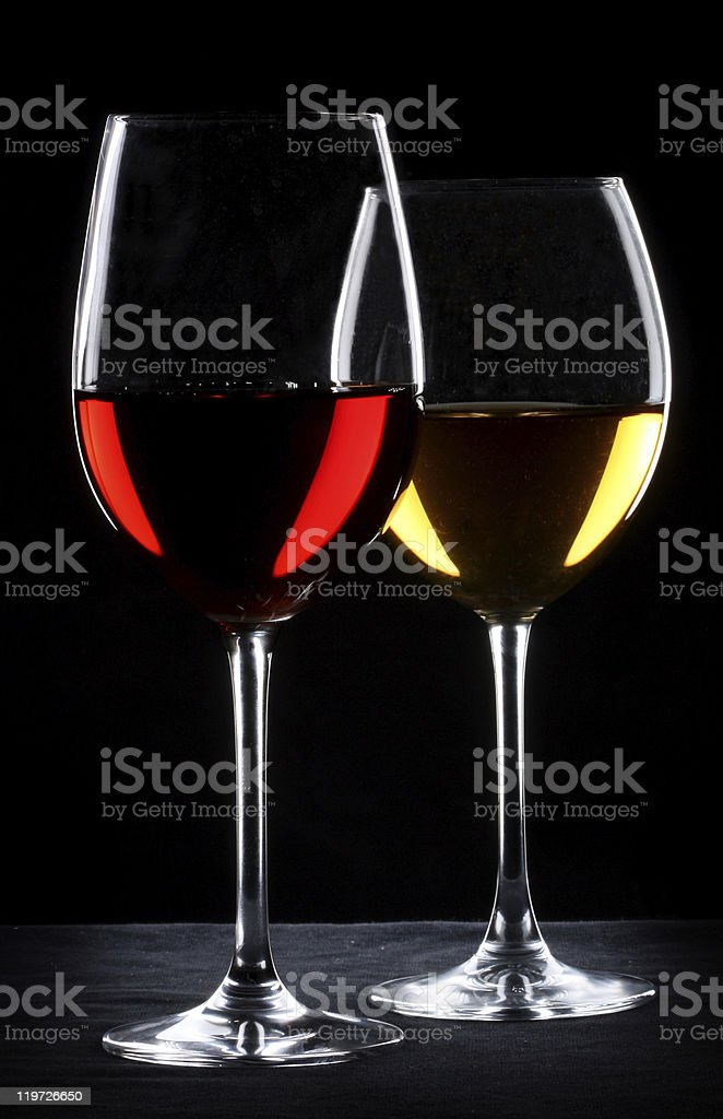 Tall glasses of red and yellow wine against black background royalty-free stock photo