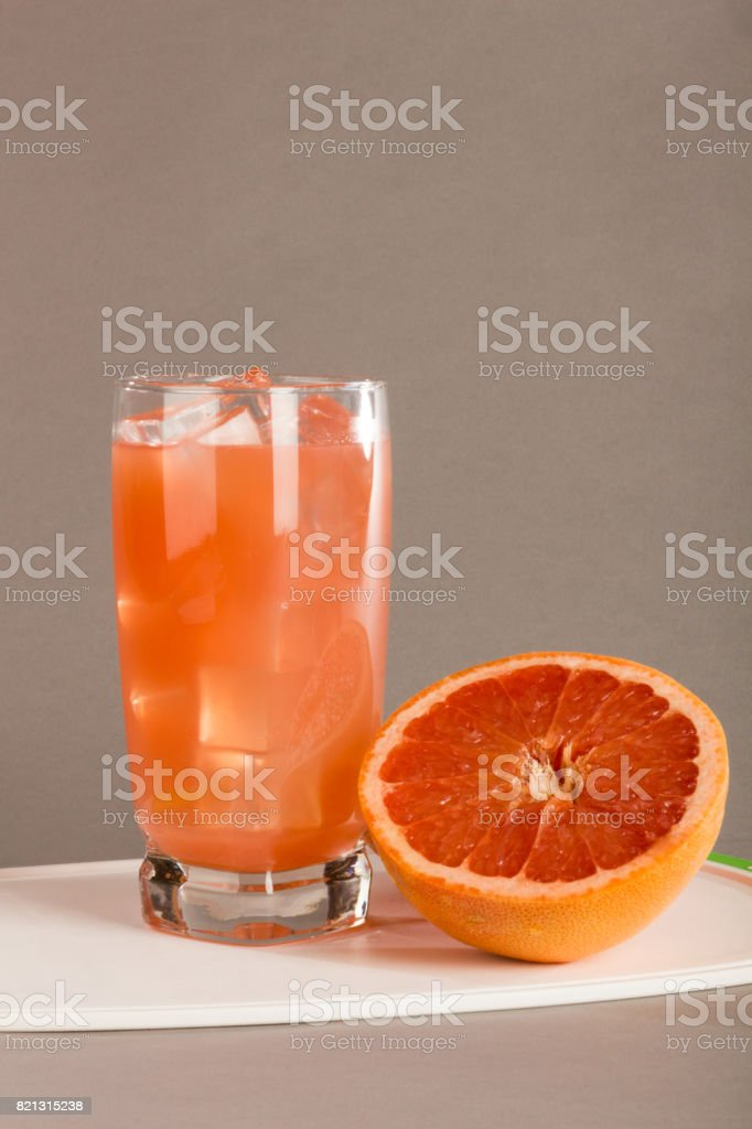 Tall Icy Glass of Grapefruit Juice with Sliced Grapefruit stock photo