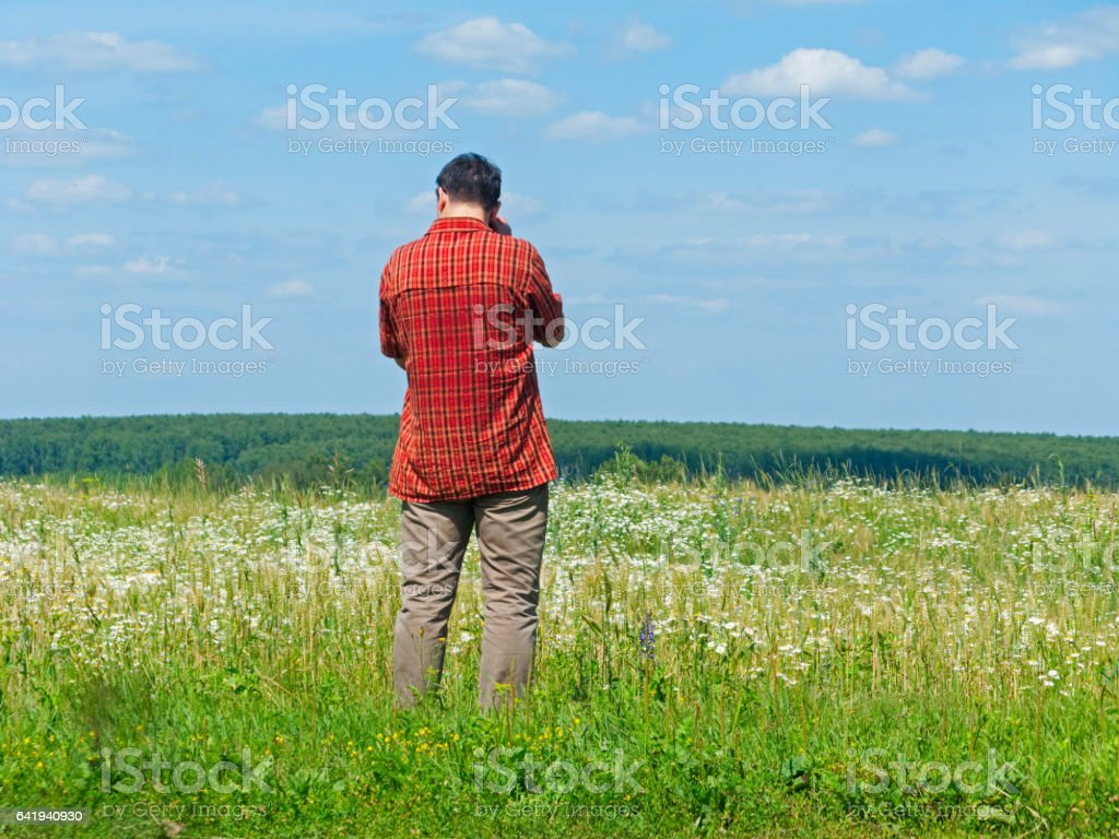 Tall man in check shirt stands back before blossoming meadow stock photo