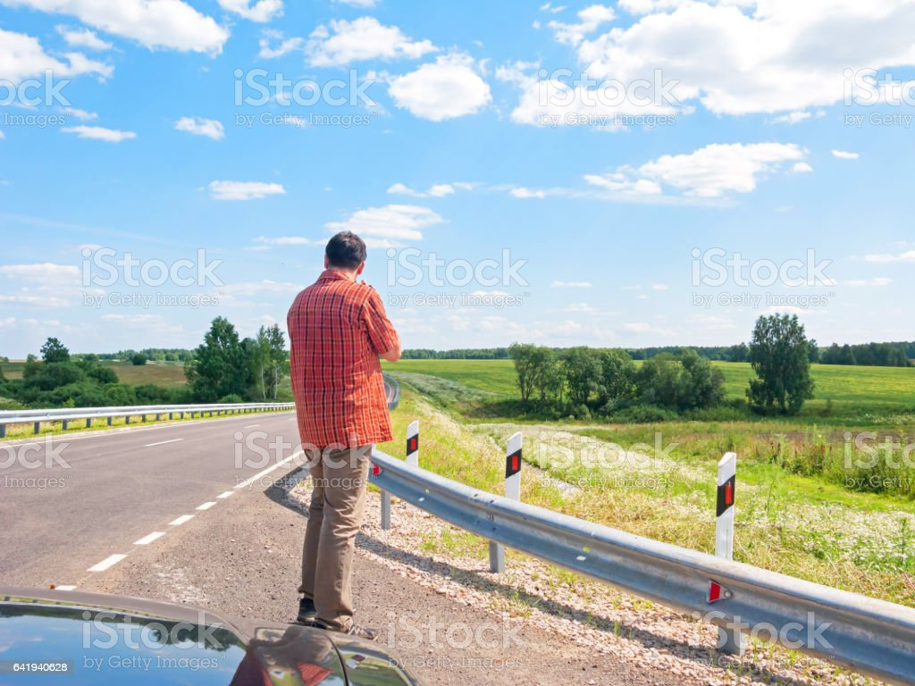 Tall man in check shirt stands back before highway turn stock photo