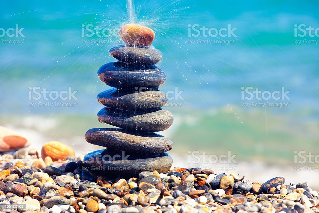 Tall pile of pebbles stacked with water drops royalty-free stock photo