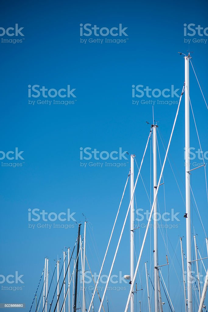 Tall sailing masts of boats against clear blue sky stock photo