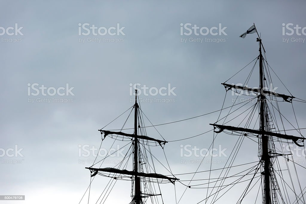 Tall ship masts against dark overcaste sky, copy space stock photo