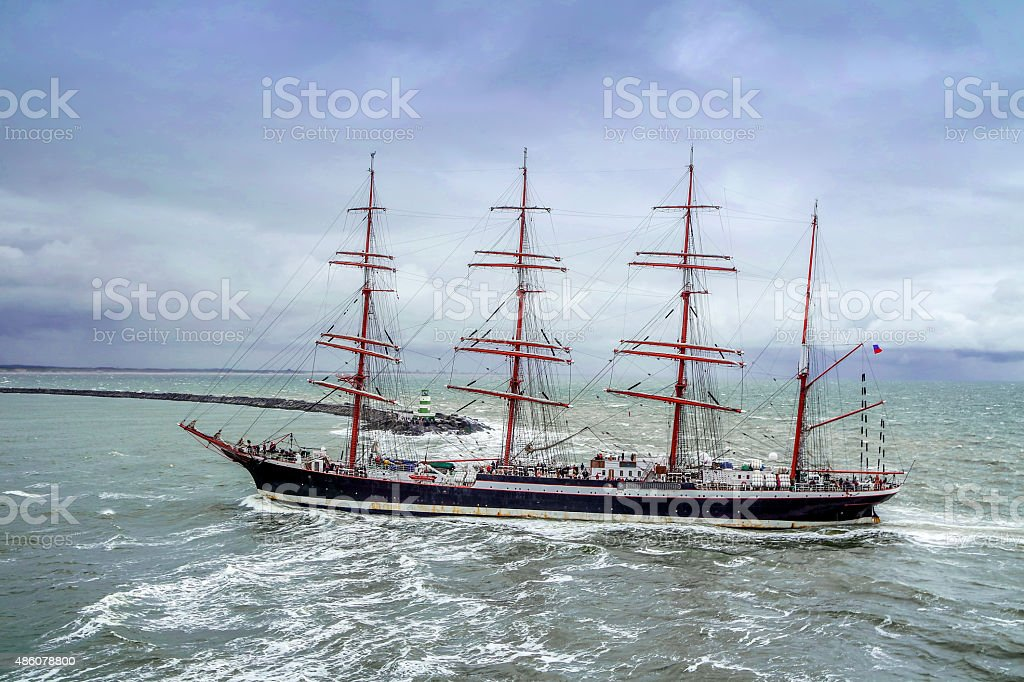 Tall ship passing a lighthouse during the rain storm stock photo