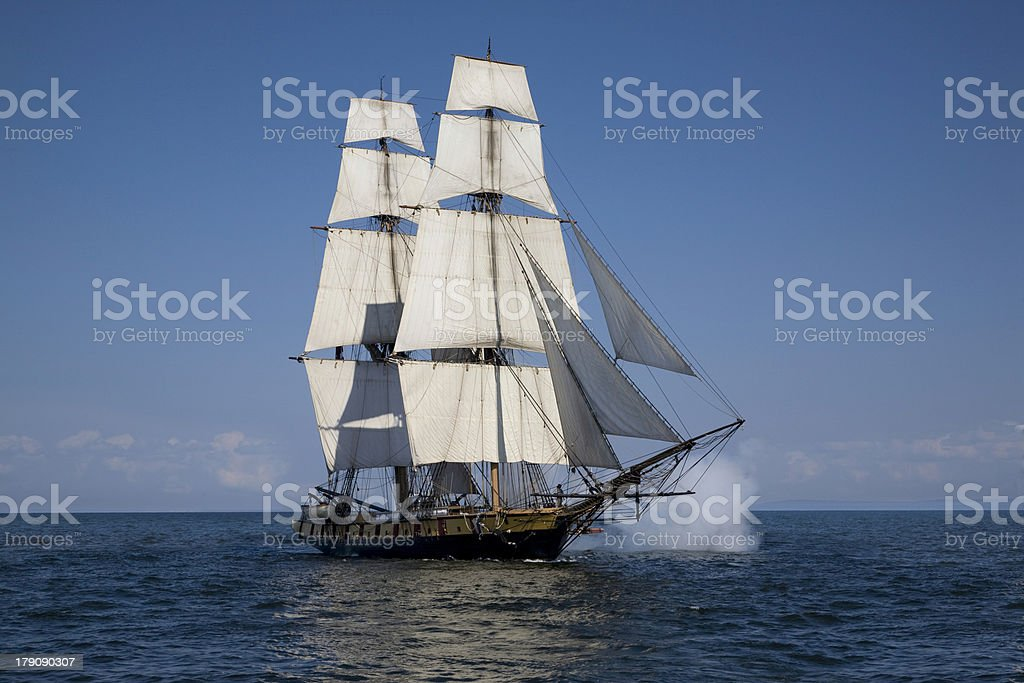 Tall ship sailing on blue waters with cannons firing stock photo