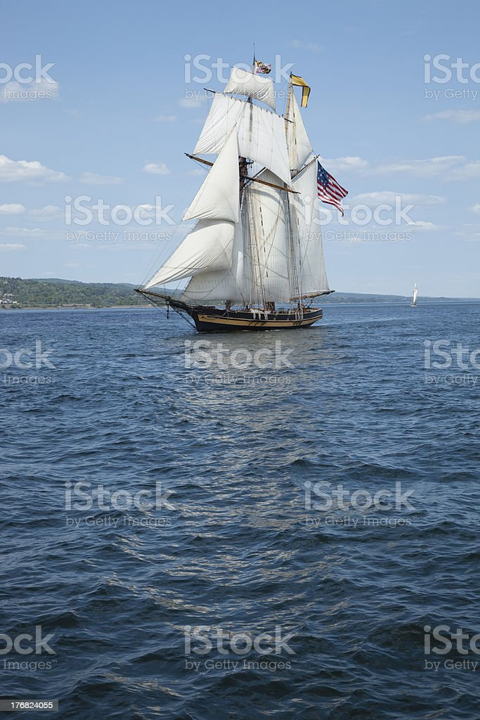 Tall ship sails on blue waters stock photo