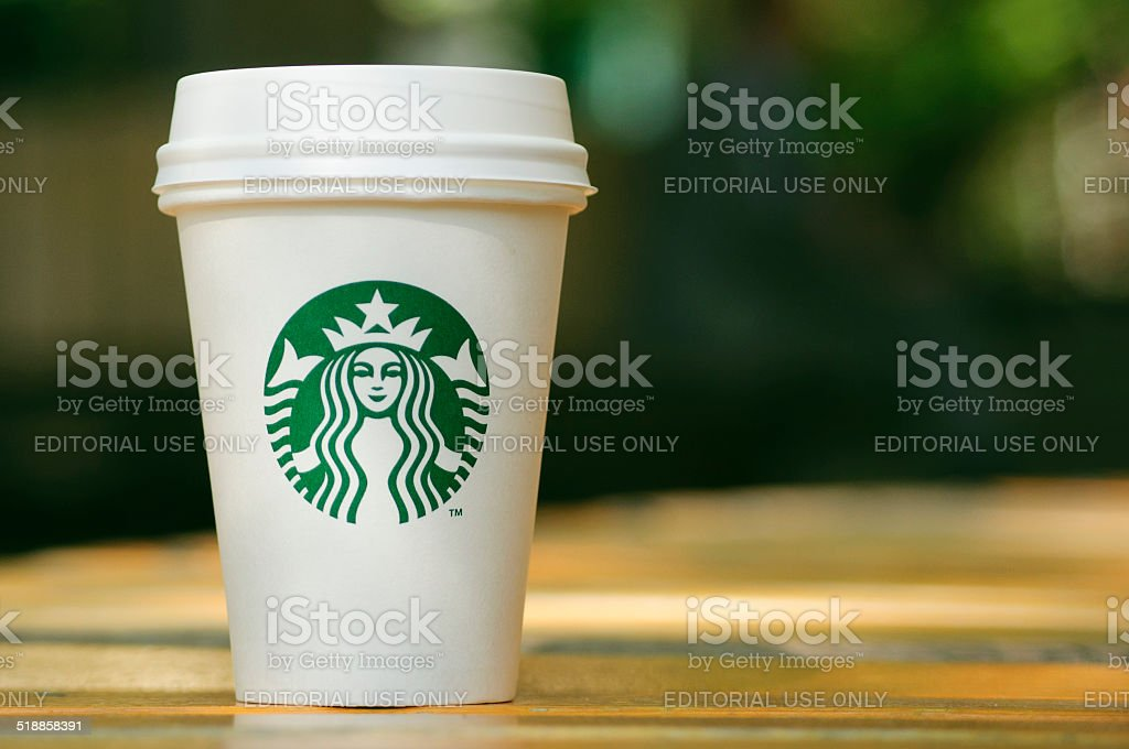 Tall Starbucks to go cup on wooden table stock photo