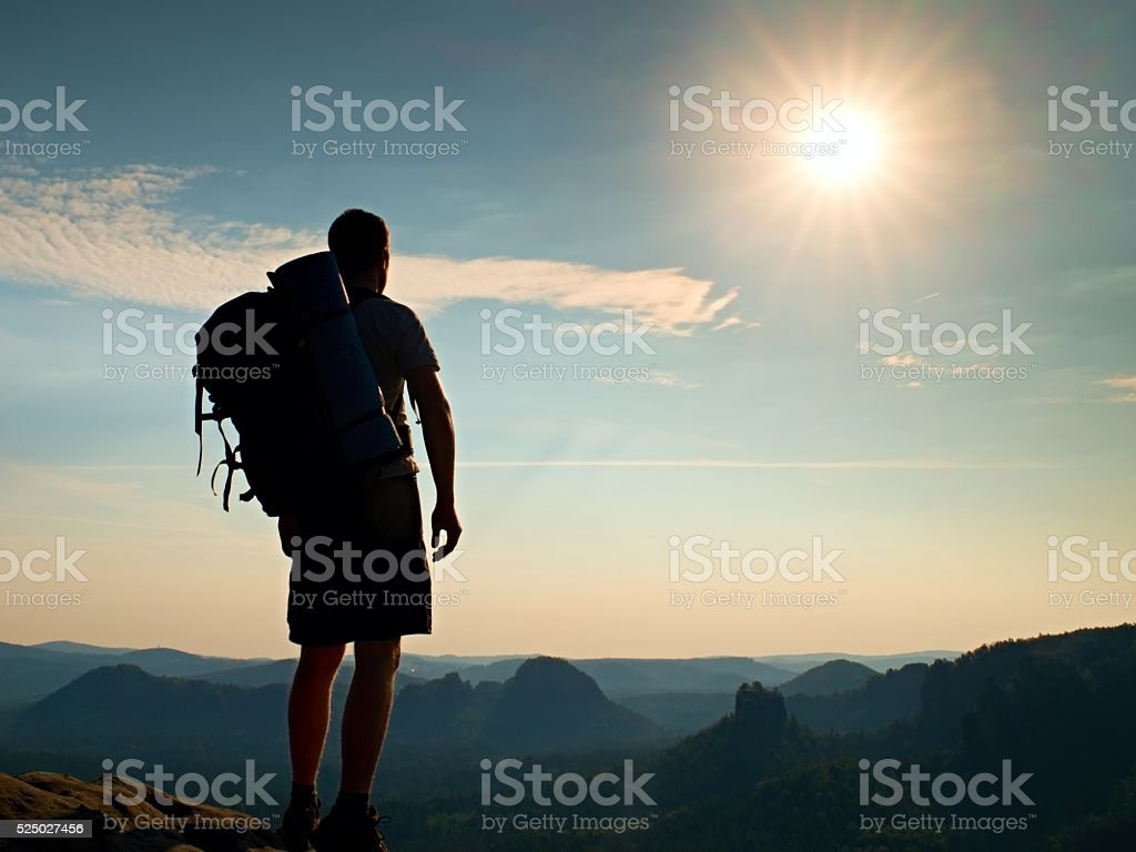 Tall tourist.  Sunny in rocky mountains. Hiker with big backpack stock photo